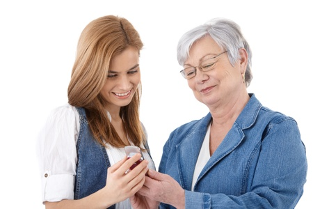 cutout old people: Senior mother and attractive daughter looking at photos on mobile phone, smiling.
