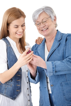 Senior mother and attractive young daughter looking at photos on mobile phone, smiling happily. photo