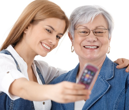 Mother and attractive young daughter photographing themselves by mobile phone, smiling happily. photo