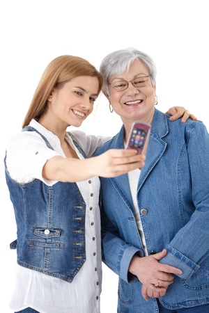 Mother and attractive young daughter taking photo of themselves by mobile phone, smiling happily. photo