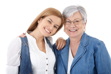 two generation family: Portrait of happy young woman and senior mother smiling over white background.