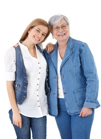 Happy senior mother and adult daughter smiling happily over white background.