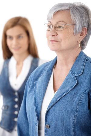 Portrait of senior woman, daughter standing at background. photo