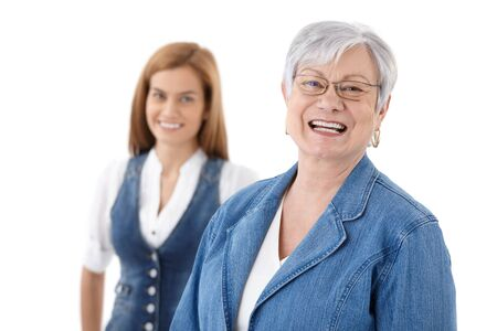 Portrait of happily smiling senior woman, daughter standing at background. photo
