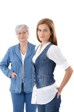 Beautiful young woman in denim waistcoat smiling, senior mother standing at background. photo