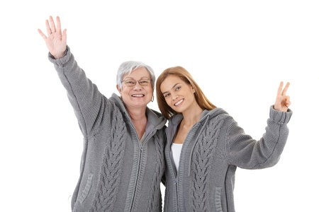 Senior mother and young daughter wearing the same cardigan, embracing each other, smiling happily. photo