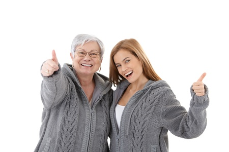 Mature mother and attractive daughter hugging each other, showing thumb up, smiling happily in identical cardigans. photo