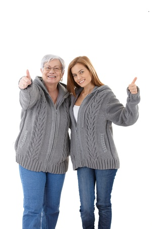 Happy senior mother and adult daughter smiling, showing thumb up. photo