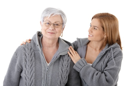Attractive young woman embracing senior mother with love, smiling, wearing identical cardigans. photo