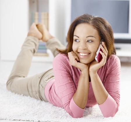 afro girl: Happy afro girl lying on floor using mobile phone, smiling.