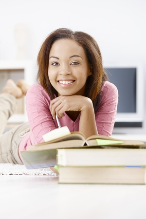 Portrait of happy afro college girl studying at home with books, smiling at camera. Stock Photo - 9255486