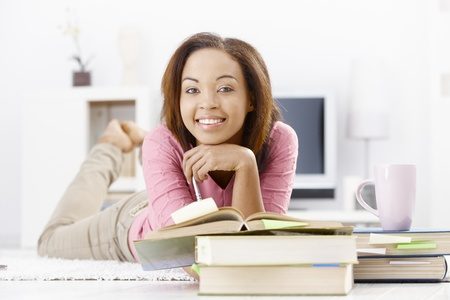University girl studying with books, lying on floor, smiling at camera. photo