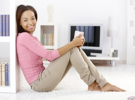 Portrait of pretty woman sitting on living room floor with tea mug in hand at home, looking at camera, smiling. photo