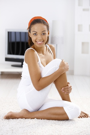 Sporty girl sitting on living room floor, stretching, smiling at camera. photo