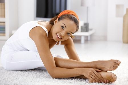굽힘: Pretty ethnic girl exercising at home, stretching and bending on floor.
