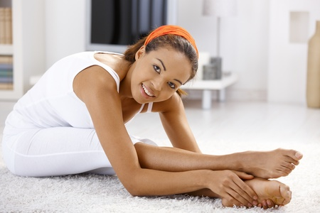 Pretty ethnic girl exercising at home, stretching and bending on floor. Stock Photo - 9249552