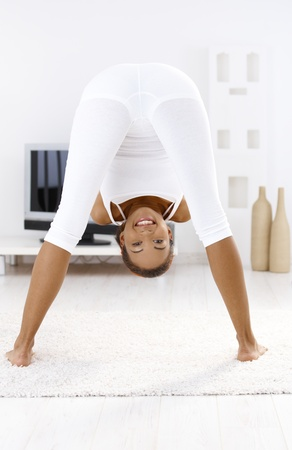 Funny portrait of smiling sporty girl looking at camera upside down while doing bending exercise. photo