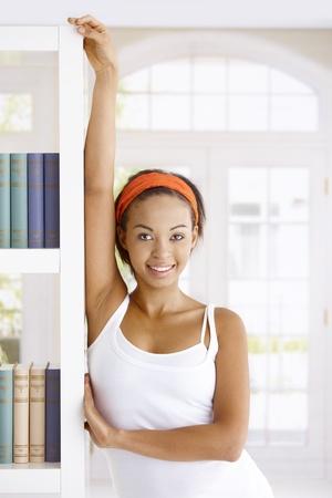 Attractive woman posing at book shelf at home, smiling at camera. Stock Photo - 9263996