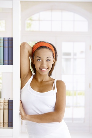 Happy afro woman posing at home, standing by book shelf, smiling at camera. Stock Photo - 9255483