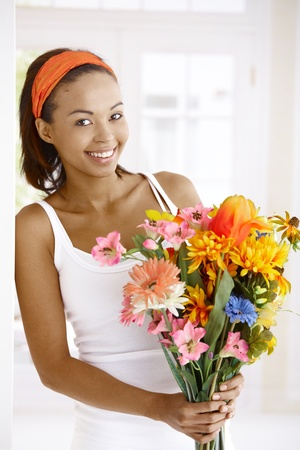 Portrait of happy woman standing with flower bouquet handheld, smiling at camera. photo