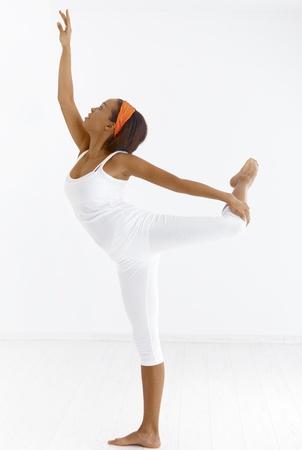 Portrait of pretty ethnic ballet dancer in pose in studio. photo
