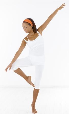 Pretty afro girl dancing ballet in studio. photo