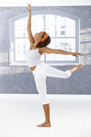 Ballet dancer girl performing in art training room, looking up. photo