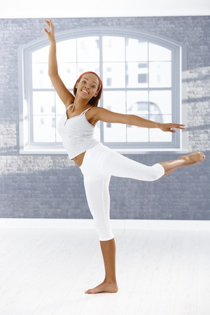 Happy ballet dancer girl in pose, smiling at camera. photo