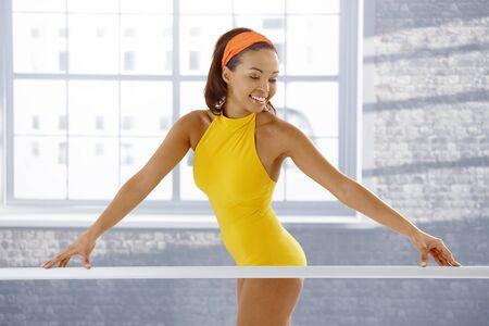 Attractive ethnic ballerina standing at ballet bar in training. photo