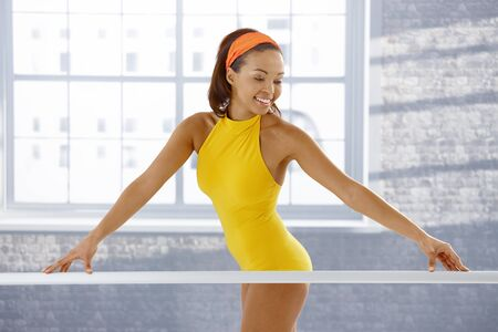 ballet bar: Attractive ethnic ballerina standing at ballet bar in training. Stock Photo
