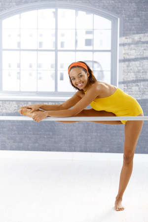 Happy pretty ballerina stretching at ballet training room, standing at bar. photo