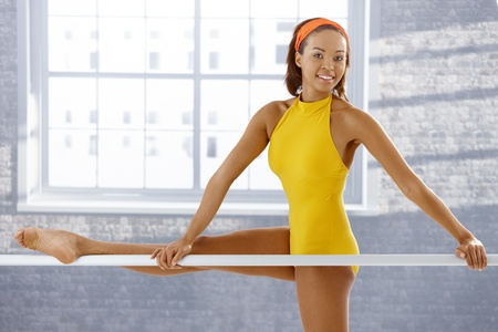 ballet bar: Portrait of attractive afro ballerina standing at ballet bar, smiling at camera. Stock Photo