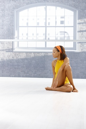 Portrait of ethnic dancer girl sitting on floor of exercise room, concentrating on training, copyspace. photo