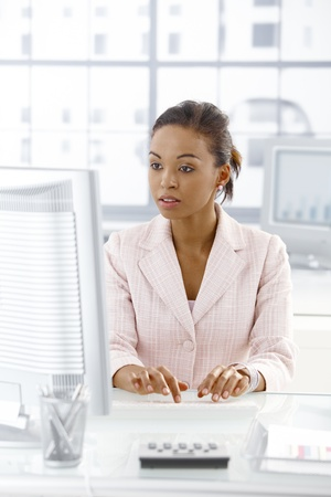 Ethnic businesswoman sitting at desk working on desktop computer, looking at monitor, concentrating. Stock Photo - 9255515