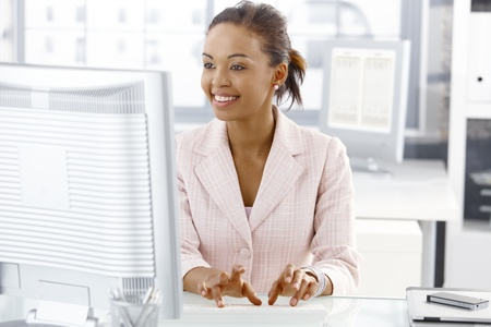 attractive office: Happy office worker girl sitting at desk, working on computer, looking at screen. Stock Photo