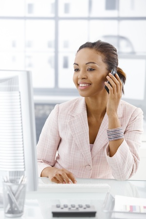 Happy businesswoman sitting at desk, looking at screen, on mobile phone call. photo