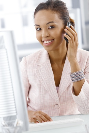 Portrait of happy office worker woman on mobile phone call, smiling at camera. Stock Photo - 9262452
