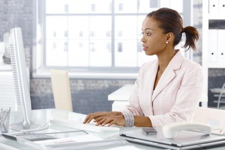 usando computadora: Atractiva afro empresaria sentado en la mesa de trabajo, utilizando equipo de escritorio. Foto de archivo