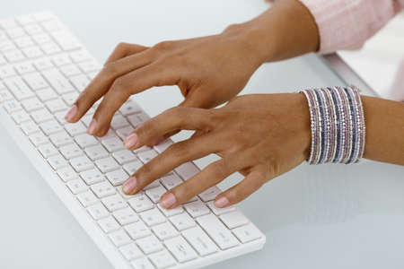 Hands of ethnic businesswoman typing on desktop keyboard. photo