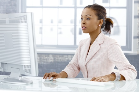 Businesswoman concentrating on computer work, looking at monitor, sitting at desk. Stock Photo - 9263997