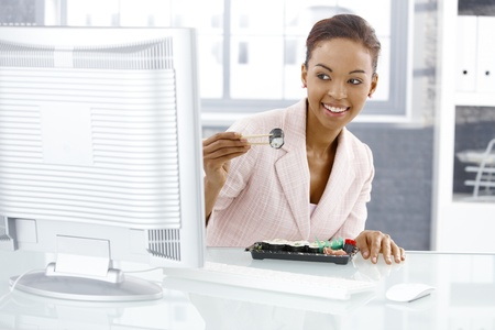 Businesswoman enjoying sushi, eating with chopstick at desk in lunch break, looking at computer screen, smiling. photo