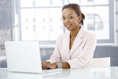 Smiling afro businesswoman using laptop computer in office, looking at camera. photo