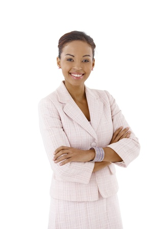 Young smart businesswoman posing in studio with arms folded, smiling at camera. photo