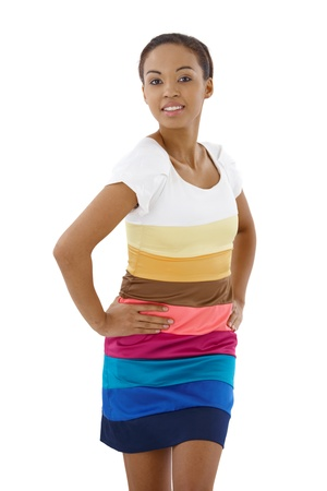 Pretty ethnic woman posing in colorful dress in studio, smiling at camera. photo
