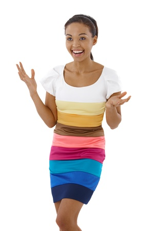 Happy surprised girl standing in multicolour dress, raising arms, laughing. photo