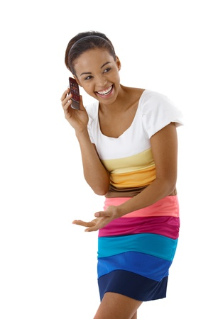 Laughing pretty girl standing in striped dress in studio on mobile phone call. photo