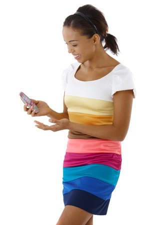Pretty afro girl standing in colorful dress, using mobile phone, laughing. photo