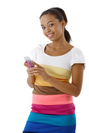 Smiling attractive afro woman standing in multicolour dress, using mobile phone, looking at camera. Stock Photo - 9249487