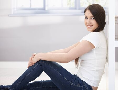 Happy college girl sitting on floor, smiling, looking at camera. Stock Photo - 9298974