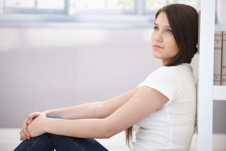 fantasize: Daydreaming young woman sitting on floor at home.